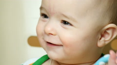 Baby boy is smiling holding a baby rattle. Stock Footage