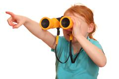 Portrait of a red haired girl with binoculars pointing upward - stock photo
