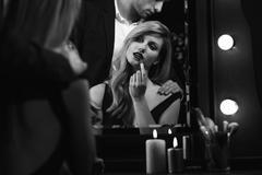 Seductive woman putting on lipstick Stock Photos