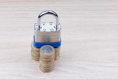 Padlock on a stack of coins - stock photo