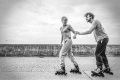 Two people race together riding rollerblades. Stock Photos