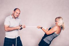 Confident man and woman pulling a rope - stock photo
