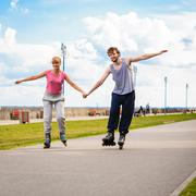 Young couple rollerblading in park holding hands. Stock Photos