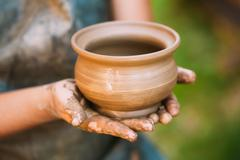Handmade of clay pot in female hands. Art and successful work, e Stock Photos
