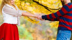 Young couple meet in park on date holding hands. - stock photo