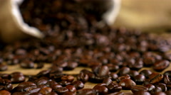 Dolly of scattered coffee beans, bag with coffee beans in the background Stock Footage