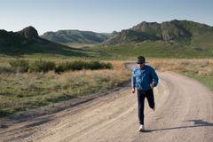 Sportsman runs on road Stock Photos