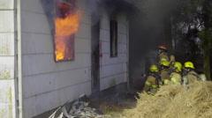 Firefights wait outside burning house Stock Footage