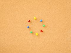 Pins in circle on notice board - stock photo