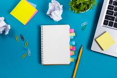 Office table desk with set of colorful supplies, white blank note pad, cup, pen - stock photo