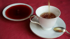 Black tea is poured into a porcelain cup of tea Stock Footage
