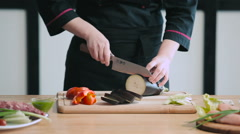 Close up of professional chef cutting eggplant - stock footage