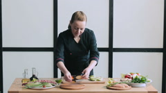 Cook lays out vegetables on the board for grilling Stock Footage