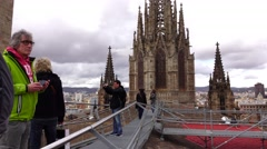 Tourists at roof of Santa Cruz Cathedral, tilt down from spiked tower to roof - stock footage