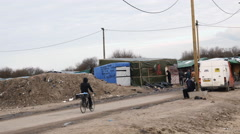 Refugee bicycling towards refugee camp in Calais, France. - stock footage