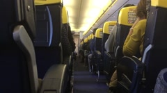 Aisle with seats and passengers in airplane Stock Footage
