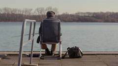 Old man fishing on chair at lakeside Stock Footage