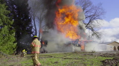 Firemen attack flames from the front Stock Footage