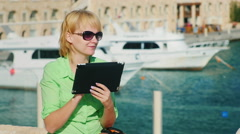 A female tourist enjoys the tablet against the backdrop of the bay with yachts Stock Footage