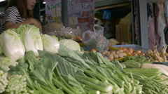 Dolly shot of Asian woman selling vegetables taking money and giving change Stock Footage