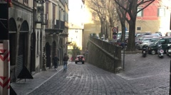 City Bergamo in Italy cars go throught bystreet along the sidewalk where people  Stock Footage