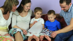 Parents with kids and grandmother consider an album with photos. Happy family - stock footage