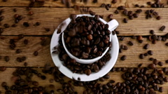 Slow motion of pouring coffee beans into a cup on an old wooden table, top view - stock footage