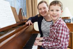 Boy With Music Teacher Having Lesson At Piano Kuvituskuvat