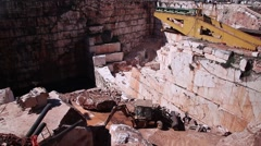 Workers working in marble stone quarry with backhoe loader Stock Footage