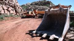 Excavator filling dump truck with excavator bucket on the floor, slider shot Stock Footage