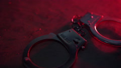 Police Arrest - Handcuffs on concrete with sirens Stock Footage