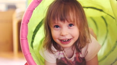 Happy little girl laughing in a children's toy tunnel - stock footage