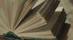Pocket Russian-English dictionary on the table in the light of the sun Stock Footage