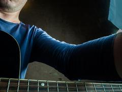 Closeup photo of an acoustic guitar played by a man Stock Photos