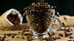 Slow motion of pouring coffee beans into a cup on an old wooden table - stock footage