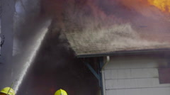 Firemen spray water on smoking and burning roof Stock Footage