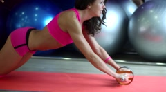 Curly girl kneels and makes complex exercises in the gym for the figure Stock Footage