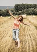 Young crazy woman imitates flying airplane at the field - stock photo