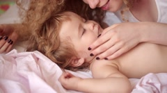 Young beautiful curly girl with love looking at the baby Stock Footage