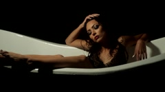 Sexy girl relaxes in the bath on a black background Stock Footage
