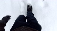 Man goes on snowy road - detail of legs Stock Footage