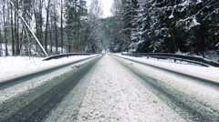 Road with blanket of snow along the forest - stock footage
