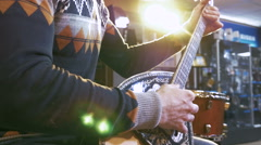 Young man playing on turkish saz guitar in the lights, 4k Stock Footage