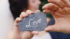 A stone with an inscription Love in the hands of a loving couple Stock Footage
