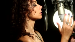 curly girl seductively caresses the microphone in the studio - stock footage