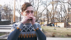 Young man playing harmonica in the park, 4k Stock Footage