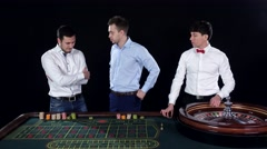 Three guys playing roulette in the casino. Black Stock Footage
