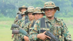 Soldiers with Weapons Stand in Line Stock Footage