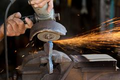 Worker grinding a metal part - stock photo