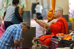 Buddhist monk blessing woman Stock Photos